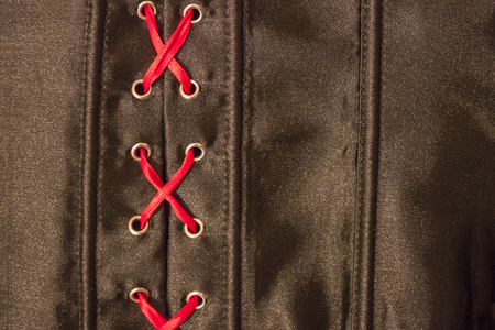 Red lacing on a black, shiny, silk background. Mystery related to personal life, sexual relations, treason.