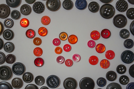 The word yes, made up of red buttons. Initiative people, positive attitude, volunteers. Around the black buttons of different sizes. Stock Photo