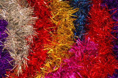 Color strips of New Years tinsel, festive mood. Merry, joyful holiday, carnival. Top view, artificial lighting.
