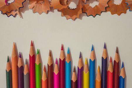 A series of sharp pencils of different colors. Readiness to work, initiative, creativity, brainstorming. Light background, top view.