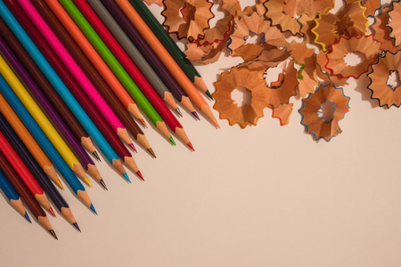 Bright, colored pencils, near a wooden shaving. Preparation for drawing, childrens creativity. Light background, top view.