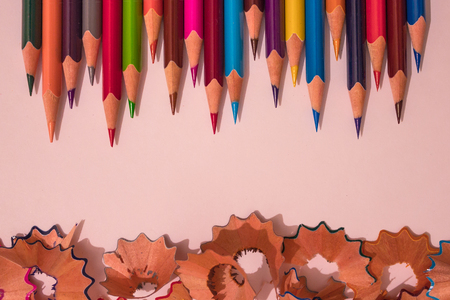 Wooden, bright, colored pencils. The rods are sharply sharpened. Above the layer of removed chips. Aim for the result, teamwork, joint creativity.