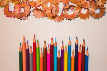 Bright pencils and wooden shavings on a light background. Stationery, school goods, supplies for drawing. View from above. Foto de archivo