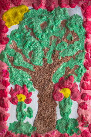 A colored postcard made by own hands. A large green tree, near by red flowers, above the sun. A gift to mom, childrens creativity. Vertical arrangement. Stock Photo