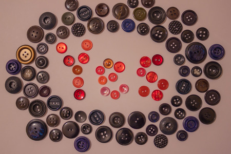 Among the dark buttons is the word yes, made up of bright red buttons. Volunteers, initiators, active people. View from above.