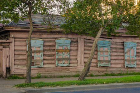 Old wooden house on a city street. The shutters are closed, the windows are boarded up. City street, in the background a modern building. Summer evening. Banque d'images
