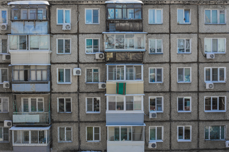 A terrible, poor apartment building built of concrete slabs. Deteriorated, cheap housing, poor housing conditions.