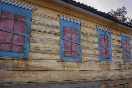 The old wooden house, the windows are shutters. Abandoned, no one else lives here. Natural lighting, summer evening.