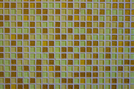 Green and yellow mosaic tiles on the wall. Chaotic order, calm background. Daylight.