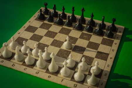 A chessboard with figures. The starting position, the first move of the white pawn. Green background, vignetting.