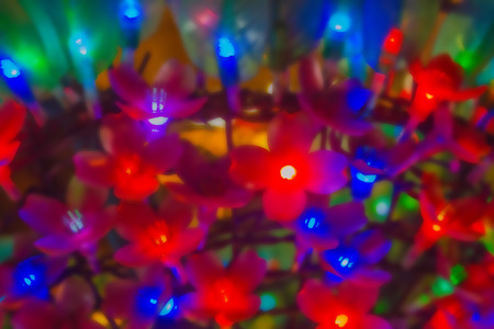 Red and blue lights are garlands, light bulbs in the form of flowers. Celebration, carnival, fun. Defocus.