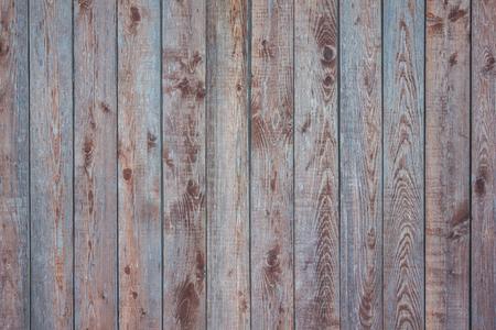 Clôture en bois, rayures verticales. Bois avec des noeuds, un motif naturel. Nuances brunes et bleues, lumière du jour. Banque d'images