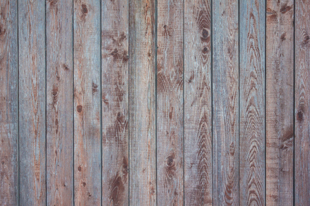 Wooden fence, vertical stripes. Wood with knots, a natural pattern. Brown and blue shades, daylight. Stock Photo