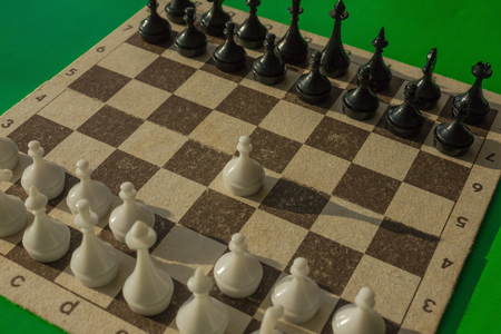 A chess field with figures. White starts. The first step, the beginning of the movement. Green background, natural light. Banque d'images
