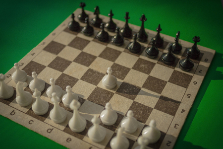 Playing chess, the beginning of the game. The first move is a white pawn. Waiting for the response step. Green background, vignetting.