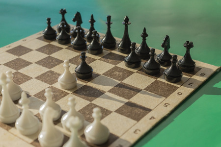 Black and white chess on a cardboard box. Game pawns begin. Green background, side sunlight. Stock Photo