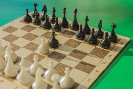 A chessboard with white and black figures. Pawns made the first move. Green background, daylight.