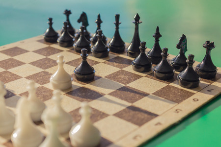 On the chessboard are arranged figures. The classic beginning of the game, the pawns in the center. Battle, confrontation. Macro photography.