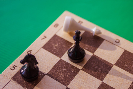 On the chessboard the defeated white king. Near the black knight and queen. Victory, defeat of the enemy, winning. Green background, warm toning, top view.
