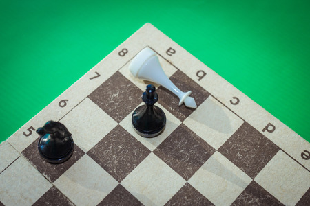 Complete defeat in chess, checkmate, deadlock. Chess pieces on the board. The king is defeated. View from above. vignetting.