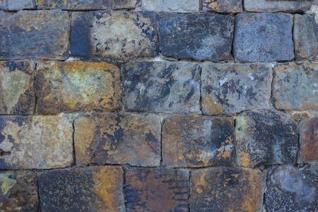 Briques faites maison de pierre sauvage. Forme irrégulière rugueuse, tons gris, noirs, bruns. Le mur d'une très vieille maison. Lumière du jour. Banque d'images
