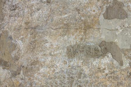 Texture d'un vieux mur de béton minable. Gris, blanc, nuances brunes, fissuré, barbouillé de copeaux. Lumière du jour.