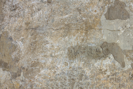 Texture of an old, shabby wall of concrete. Gray, white, brown shades, cracked, smeared with chips. Daylight.