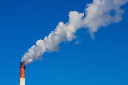 Un grand tuyau fumant sur le fond d'un ciel clair et sans nuages. Mauvaises conditions environnementales, dommages à la nature, émissions nocives dans l'atmosphère, pollution de l'environnement.
