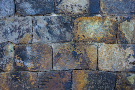 Ancient brickwork. Bricks are hewn out of untreated stone. Rough, textured surface. On the stones are black traces of fire. An old house.