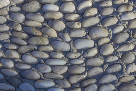 Element of landscape design, street decoration. Round smooth stones are laid in a concrete surface. Natural pebbles, handmade. Banque d'images