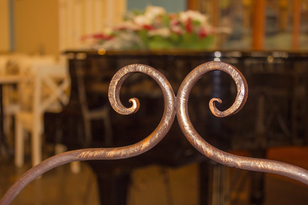 Decorative element made of bronze, handmade. Interior of an old cafe, restaurant, salon. In the background, a black grand piano, white tables and chairs. The background is blurred.