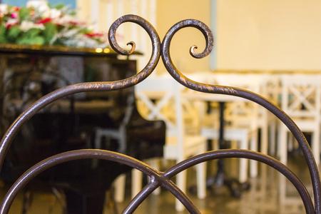 Dos d'une ancienne chaise en bronze forgé, production artisanale. En arrière-plan, il y a un piano à queue et des meubles en bois blanc. Intérieur vintage du café. Matin, lumière naturelle. Banque d'images