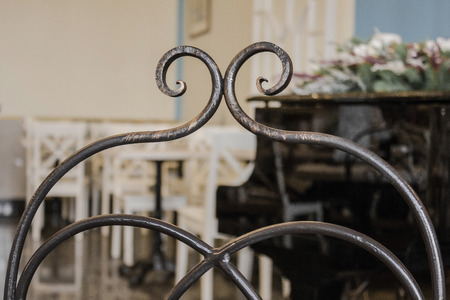 Retro style, old cafe, vintage furnishings. Close-up decorative element of wrought iron, handmade. Muted tone, natural lighting. Stock Photo