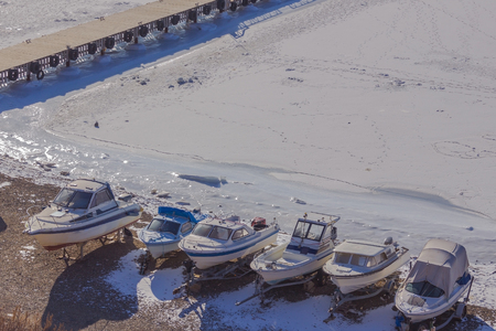 Boats hibernate on the snowy seashore. The water froze, its cold. A pier is in the distance. There are many traces on white ice. Bright sunlight.