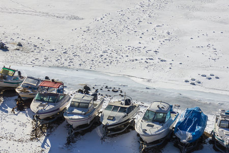 Boats in the snowy harbor. Around the frozen sea, white ice. Marina, parking for yachts, boat station. Spring is coming. Bright sunlight.