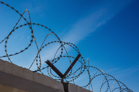 A fence with barbed wire against the background of a bright blue sky. Lack of freedom, bondage, punishment for a crime. Solar lighting, view from below. Stock Photo