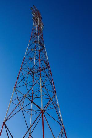 Toren met elektrische draden. Overdracht van elektriciteit, verbinding met de lijn. Heldere blauwe lucht. Onderaanzicht.