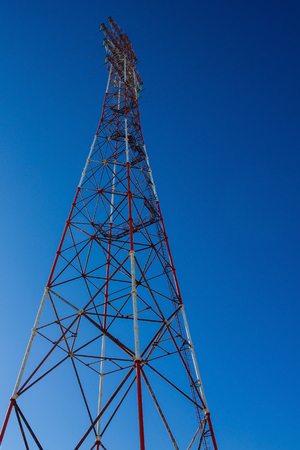 Tower with electric wires. Transmission of electricity, connection to the line. Bright blue sky. Bottom view.