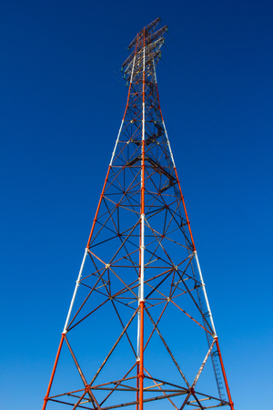 High tower, power line support. Bottom view, bright sunlight. Vertical arrangement. Фото со стока