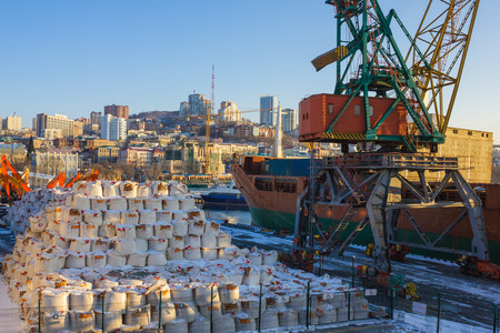 Sea cargo port in a modern city. On land, a large consignment of bags, next to a crane. Loading, transportation of goods on the ship. Morning, sunlight.