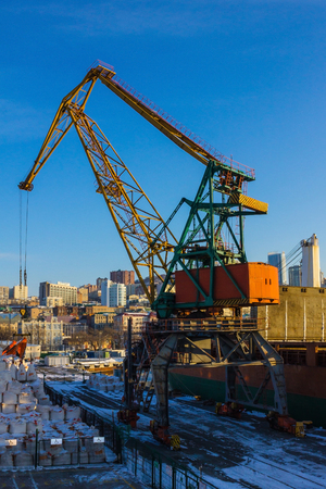 Crane operation in the seaport. Freight terminal in a modern city. High buildings in the distance. The blue sky, clear sunny morning. Vertical arrangement.