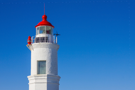 Against the background of a clear blue sky, the round tower of the operating lighthouse. An old building of white brick. Red dome with a spire. Tells seamen the right way.