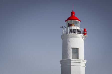 An old sea lighthouse made of white bricks. At the top is a red lantern. The sign of the right road. Day, sunlight, bottom view, vignetting.