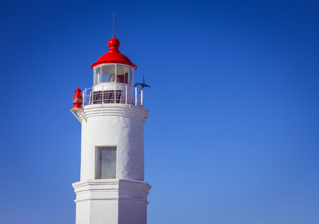 The tower of an old lighthouse, made of white brick. Red roof with a spire, on top of a weather vane and a solar battery. Bright solar illumination, vignetting.