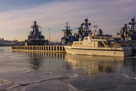 Many modern ships of gray color stand in the roadstead near the seaside city. Military fleet, flotilla. Cold season, the water is covered with thin ice. Lateral solar illumination.