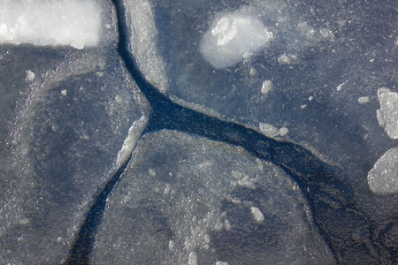 Transparent ice, under it dark water. On the surface of large cracks. Early spring, warming. Solar lighting, top view.