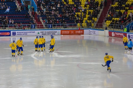 Khabarovsk  Russia - 01.31.2018: Swedish hockey team in yellow uniform on the ice arena. Warm up before the second period. In the background, stands with spectators.