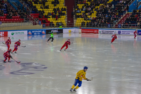 Khabarovsk  Russia - 01.31.2018: The Swedish and Russian teams play at the World Bandy Championship. Red and yellow forms of players. In the stands spectators, fans.