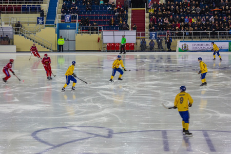 Khabarovsk  Russia - 01.31.2018: The Swedish team in yellow uniform, the Russian national team in red. Players with sticks on ice, away referees and spectators. The game moment.