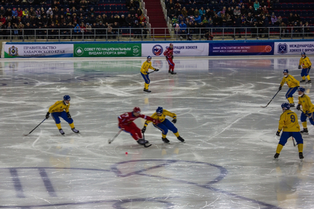 Khabarovsk  Russia - 01.31.2018: The Swedes play with Russia. A dangerous game moment. Swedes in tight defense, the Russian player has a ball. In the background stands with fans.